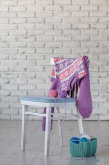 Baby girl sweater hanging on white brick wall wall