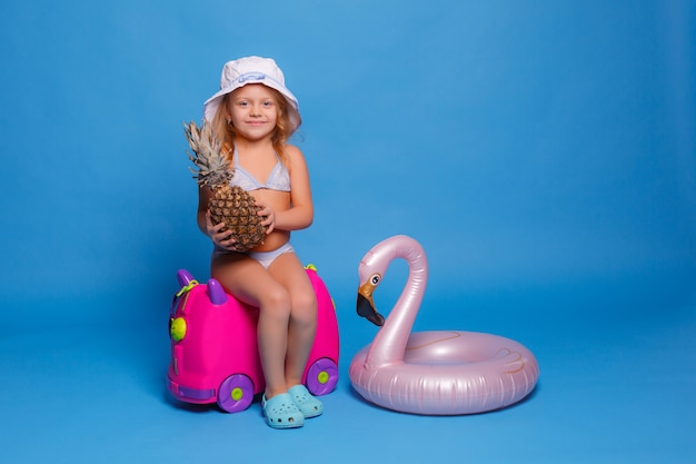 A baby girl in a swimsuit with a pineapple in her hands sits on a suitcase on a blue background. travel concept