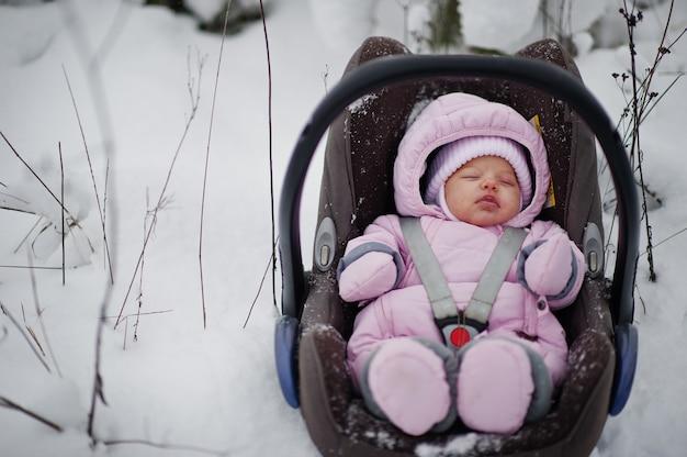 冬の日に車の椅子で女の赤ちゃんの幼児。雪の降る寒い日の公園で。