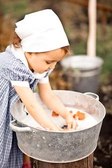 ブリキの洗面器で人形を洗う女の赤ちゃん。レトロなスタイル。田舎のコンセプト。
