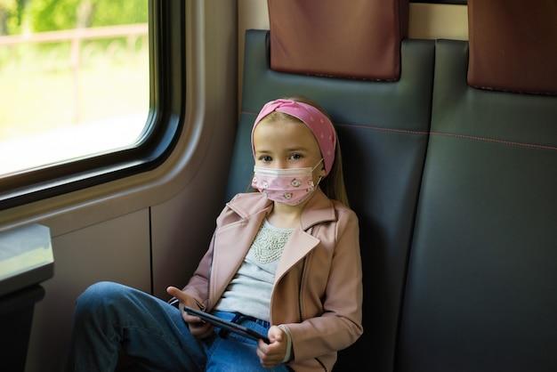 일회용 마스크를 쓰고 아기 소녀는 현대 기차의 좌석에 앉아