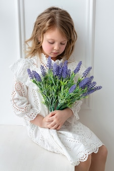 A baby girl in a white dress with flowers on a light windowsill covered in natural light.