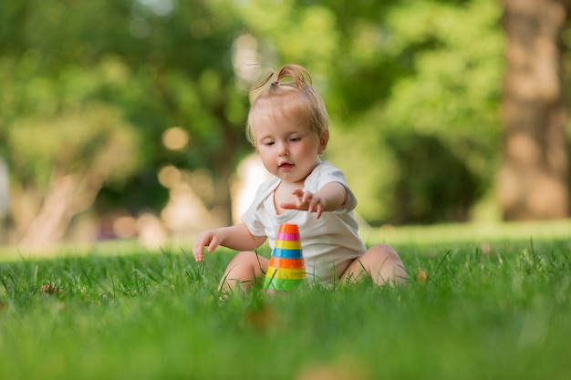 Baby girl in a white sandpit on the green grass playing pyramid