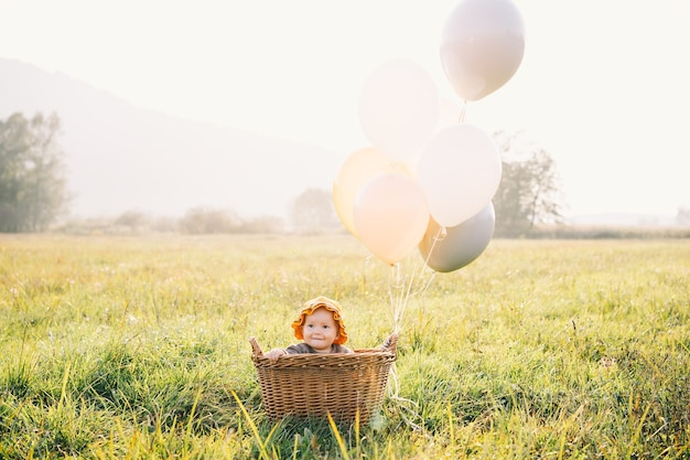 Baby girl in wicker basket with balloons in sunlight in autumn time