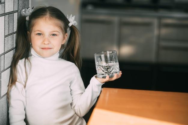 彼女の手に水のガラスを持つ女の赤ちゃんはとても甘い