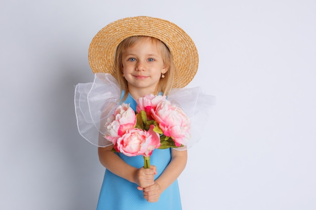 Baby girl with a bouquet of flowers and a straw hat