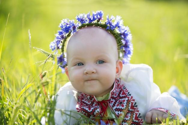 刺繍でヤグルマギクを持つ女の赤ちゃん。ベラルーシのシンボル