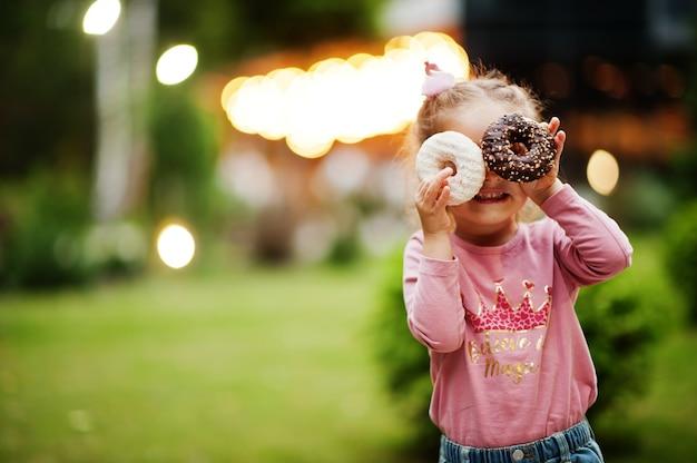 夜の庭でドーナツを持つ女の赤ちゃん。おいしいおいしいドーナツ料理。