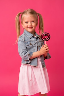 Baby girl with lollipop on pink background