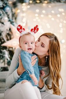 크리스마스 트리 근처 바닥에 엄마와 아기 소녀. 새해 복 많이 받으세요 그리고 메리 크리스마스