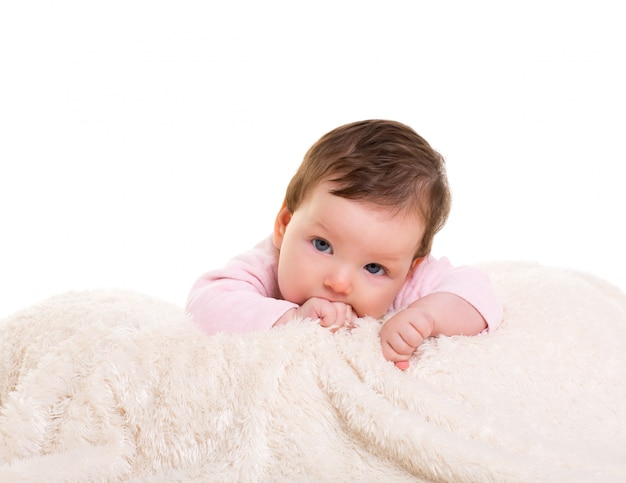 Baby girl with toothache in pink with on white fur