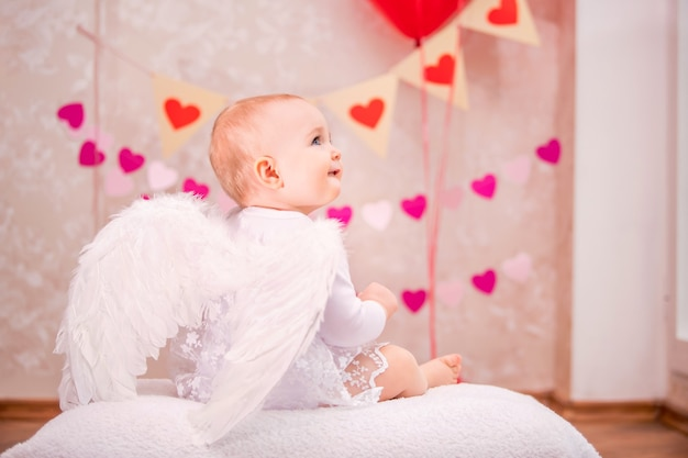흰색 깃털 날개를 가진 아기 소녀는 발렌타인 데이 기호, 뒤에서 볼 수있는 흰색 부드러운 베개에 앉아 있습니다.