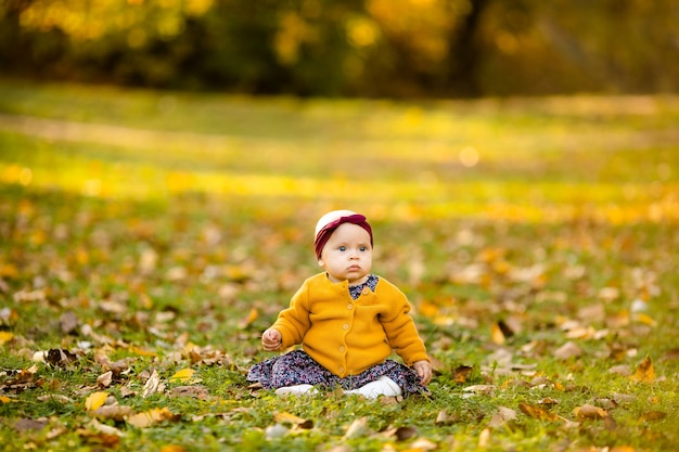 Baby girl in yelloy jacket and red headband seating on the grass