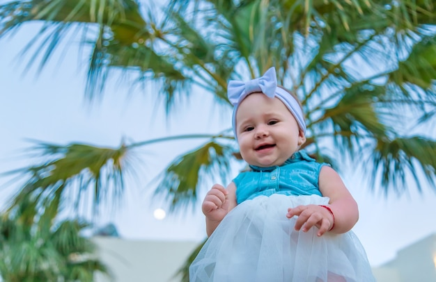 Baby on the grass sits under a palm tree