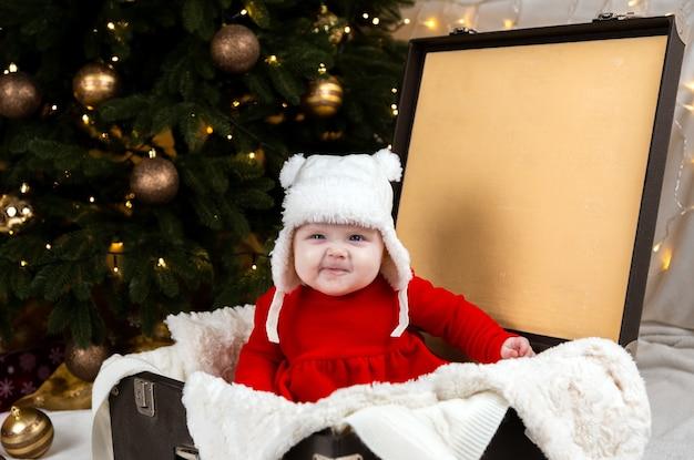 赤ちゃんのしかめっ面と古いスーツケースに座っています。赤いクリスマスドレスと白い帽子をかぶった子供がスーツケースに座って感情を表現します