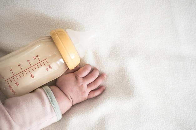 Baby hand and bottle of mother breast milk