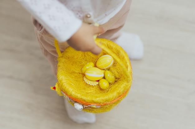 赤ちゃんの手は黄色い卵のバスケットを持っています Premium写真