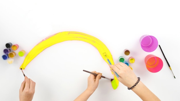 아기 손은 흰색 바탕에 무지개를 그립니다. 아이들의 창의력과 취미