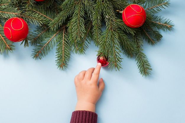 Baby hand with christmas decor on blue winter , copyspace