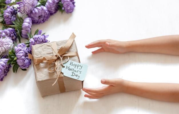 Детские руки и подарочная коробка маме на день матери, на белом фоне со свежими цветами хризантемы.