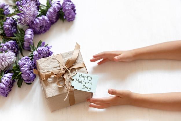 어머니의 날을 위한 아기 손과 선물 상자는 신선한 국화 꽃이 있는 흰색 배경에 있습니다.