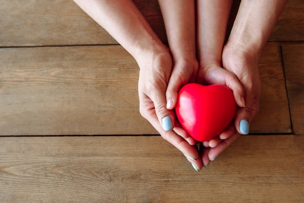 Baby hands and female mother's hands together hold a red heart on a wooden scene with free space under the text