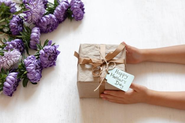 Mani del bambino e confezione regalo per la mamma per la festa della mamma, su uno sfondo bianco con fiori di crisantemo freschi.