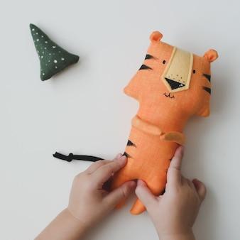 白い背景の新年とクリスマスに新しいの面白い小さな虎のおもちゃのシンボルを保持している赤ちゃんの手...