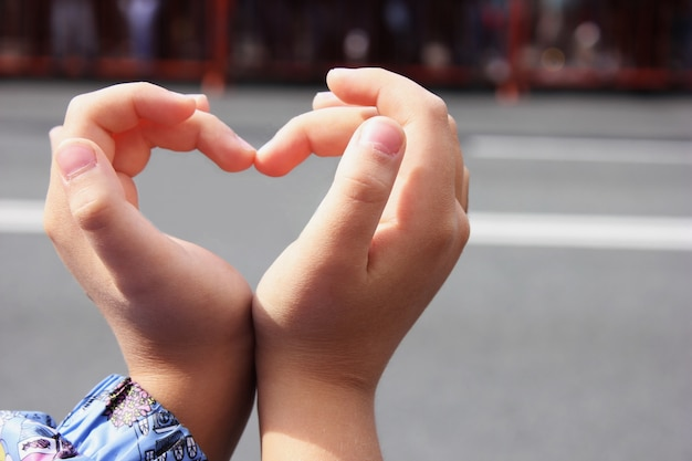 Baby hands made heart by folding fingers.