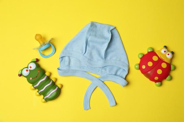 黄色の背景に赤ちゃんの帽子とおもちゃ。