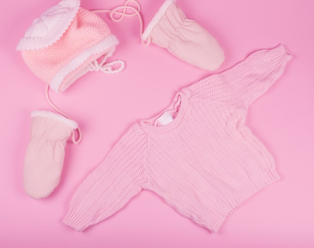 Baby hat, mittens and sweater of pink color