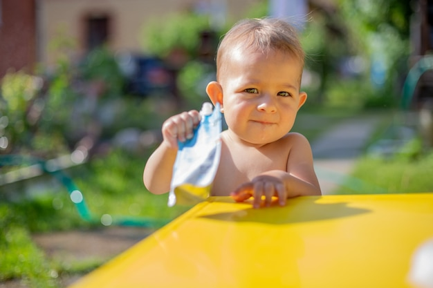 赤ちゃんはカメラを見てポーチにフルーツピューレを保持し、黄色のテーブルの前にカメラにそれを与えます