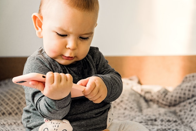 Baby hold phone sitter toddler indoors early technical development genz concept