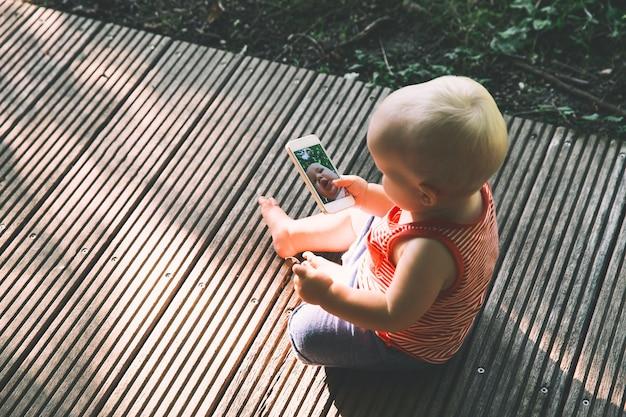 携帯電話を持って、携帯電話のカメラで面白い自分撮りをしている赤ちゃん