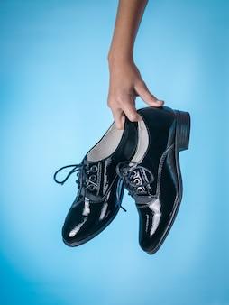 Baby holding fashionable black leather shoes on blue