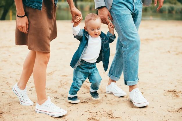 公園を歩こうとしている彼の母親と父親の手を握って赤ちゃん
