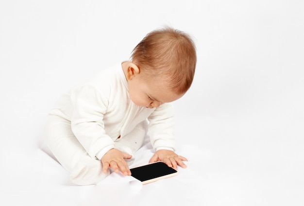 Baby holding a mobile phone isolated on white background generation z