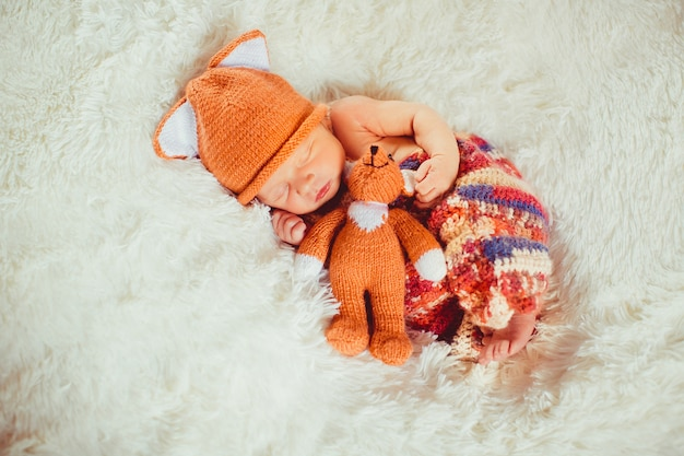 Baby holds little fox toy sleeping on the white pillow