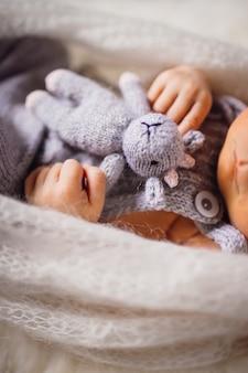 Ребенок держит игрушечную корову, лежащую на пушистой подушке