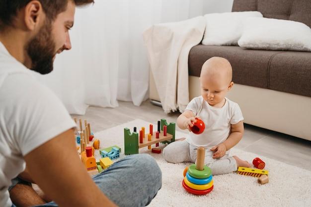 Bambino a casa che gioca con suo padre