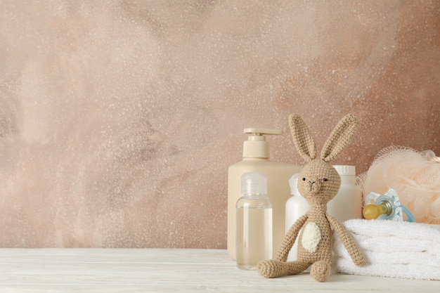 Baby hygiene accessories on wooden table against brown wall