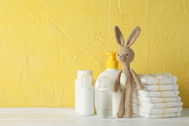 Baby hygiene accessories on wooden table against yellow wall