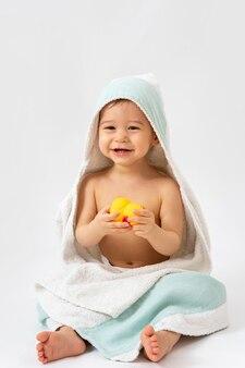아기 위생 및 관리. 목욕 후 두건이있는 수건에 싸서 귀여운 유아 소년.