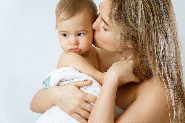 아기 위생 및 관리. 젊고 행복한 어머니와 목욕 후 그녀의 귀여운 유아 아들.