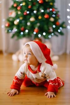 Младенец в новогоднем костюме и шапке санты ползет перед елкой. фото высокого качества