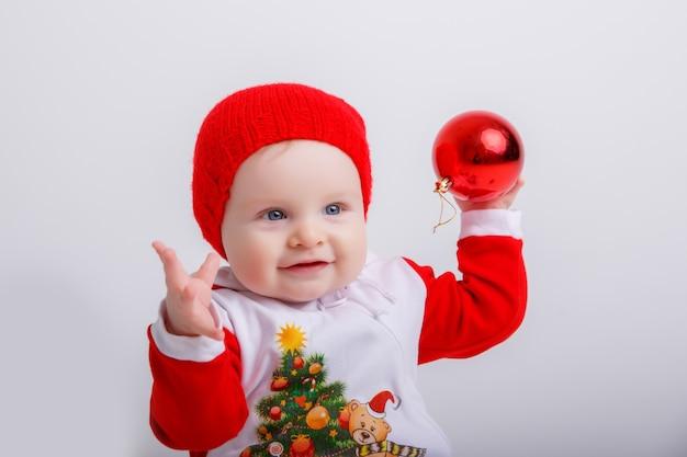 Ребенок в костюме рождественского гнома держит рождественский глобус