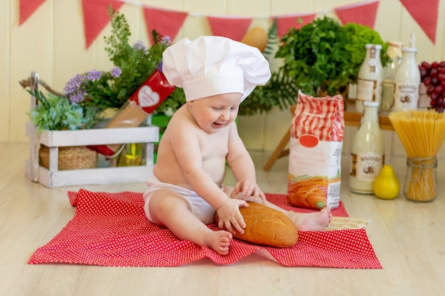 彼の周りに食べ物を持つコック帽子の赤ちゃん