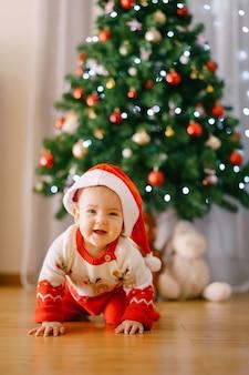Малышка в вязаном костюме оленя и шапке санты ползет перед елкой. фото высокого качества