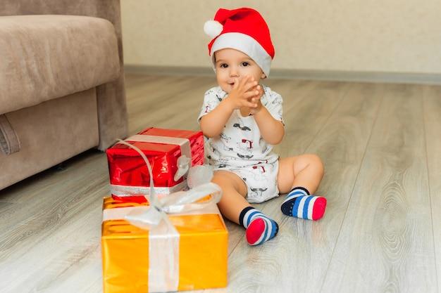 Ребенок в новогодней шапке сидит на полу и держит в руках подарки.
