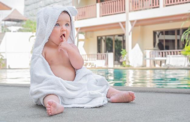Младенец в полотенце. ребенок сидит на краю бассейна